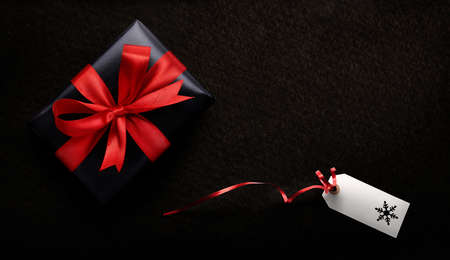 A Christmas present wrapped in black paper and red ribbon with a blank tag, card against a dark background from above. Stockfoto