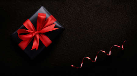 A birthday, Christmas or valentines gift, present wrapped in black paper and red ribbon on a dark background from above. Stockfoto