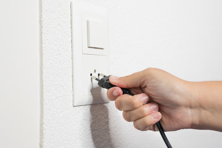 A womans hand pulls a black cord from the socket.