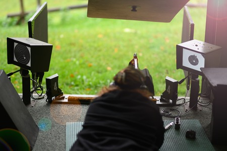 Woman with assault rifle on a shooting range in Switzerland