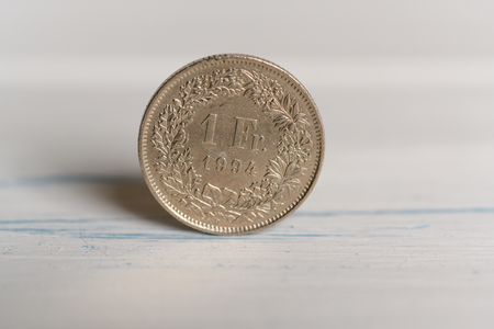 A 1 Swiss Franc coin standing on a wooden background