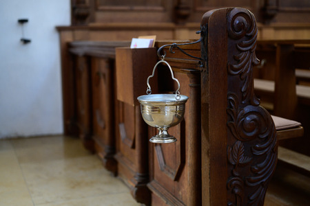chalice with holy water to the cross on entering a church