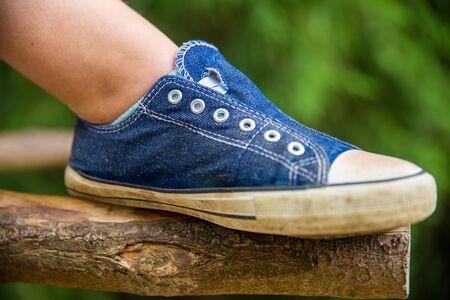 A blue sneaker without shoelaces taken outside Фото со стока