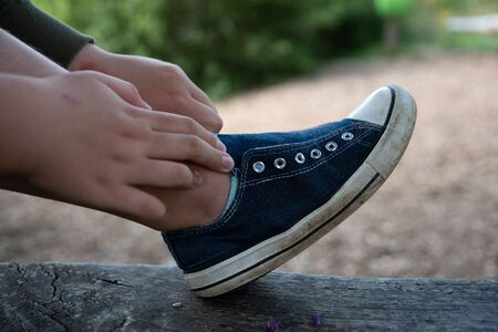 A childs hand grabs the foot with a blue shoe