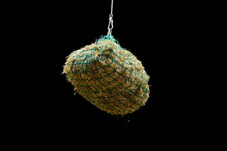 Hay bales suspended in a net on a chain