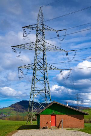 An electricity pylon in front of a small house in Switzerland Фото со стока
