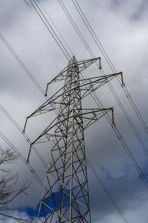 Dark clouds pass over an electricity pylon.