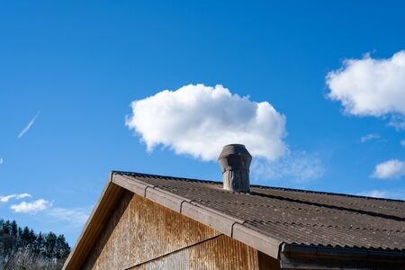 A chimney with a small white cloud
