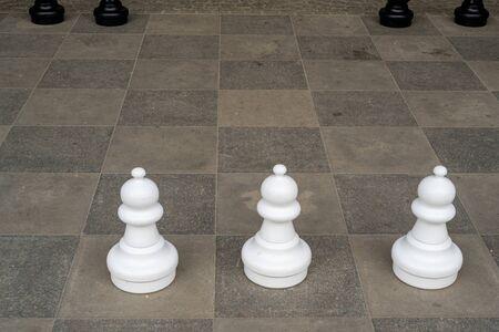 three white pawns on a chess board Фото со стока