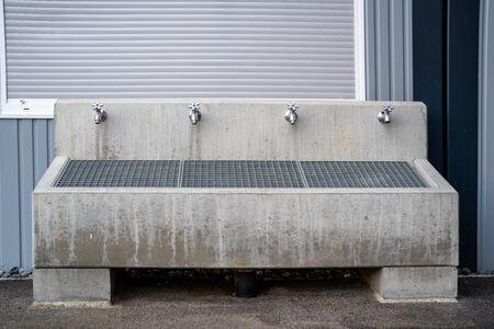 Fountain with a grate and 4 taps to clean shoes