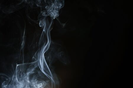 Abstract smoke from incense and light in a black background