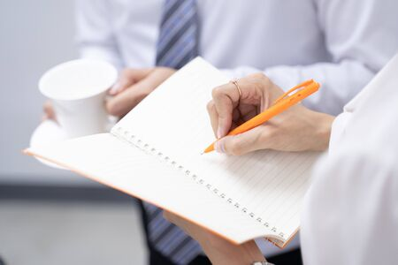 A business person is holding a pen and notes on the assignment