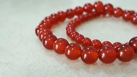 glow: Red stones bracelets on grey background
