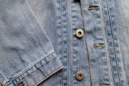 bottons: Close up aged denim texture. Old blue jeans jacket with stiched and vintage bottons.