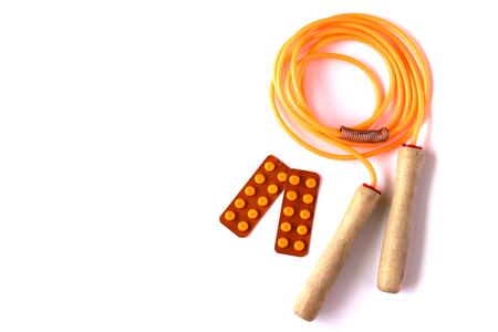 saltar: Naranja saltar la cuerda con ampollas de píldoras en el fondo blanco. concepto de vida saludable.