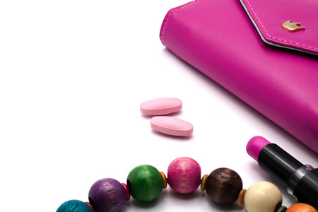 lip stick: Pink vitiamin tablets with magenta purse, lip stick and necklace on white background. Women health concept. Stock Photo