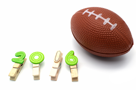 Isolated american football toy and number 2016 on white background.