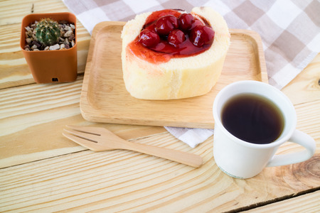 Cup of hot espresso coffee with strawberry cake roll on wood table. Stock Photo