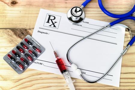 blanked: Doctor work table desk with red injection syringe, medical blister of red and black capsule pills , stethoscope and prescription sheet blanked for diagnosis information. Stock Photo