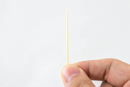 toothpick: Hand holding a toothpick Stock Photo