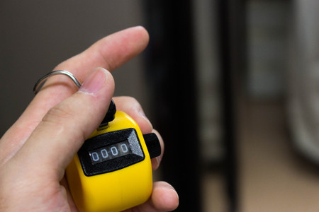 clicker: hand holding a yellow counter machine Stock Photo