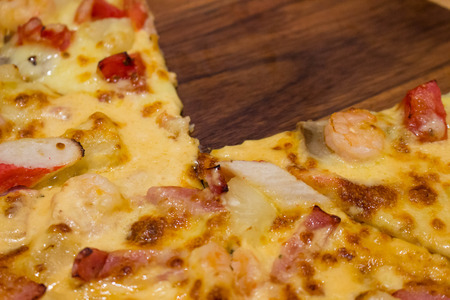 cut off: Pizza on circle wooden plate with one slice cut off