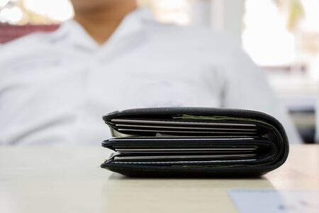 Black thick wallet on wooden table