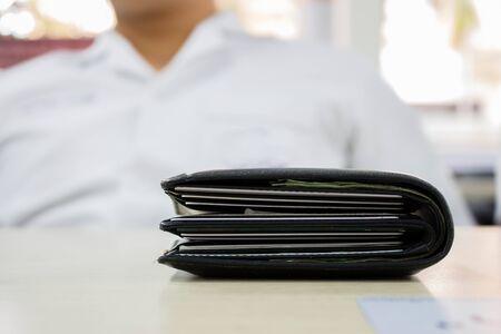 Cartera gruesa negra sobre mesa de madera