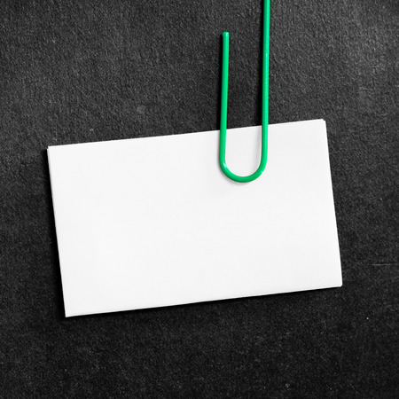 Paper clip clipping white paper on black background