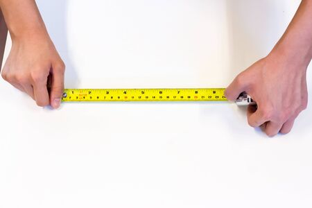 deign: tape-measure in hand with white background