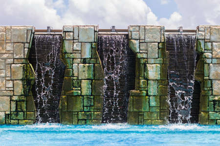 gush: Three fountain down to water pool and cloudy sky Stock Photo