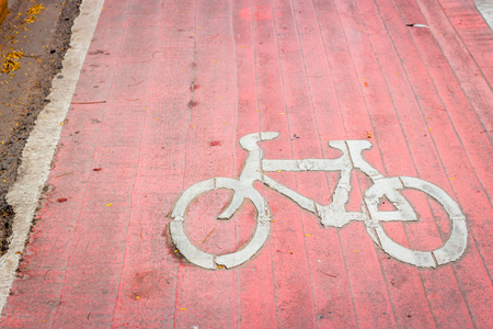bikeway: Old red bicycle lane with white bicycle sign on the ground around the park