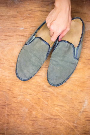 grabing: Hand grabing a pair of old green shoes from wooden floor