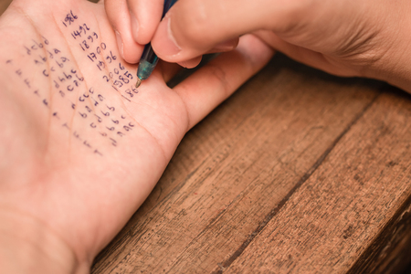 People cheating on test by writting answer on left hand Standard-Bild