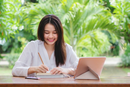 Happy asian woman working on wooden table with blurry tree background Banque d'images