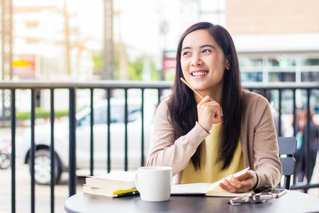 Happy asian woman smiling while working Stock Photo