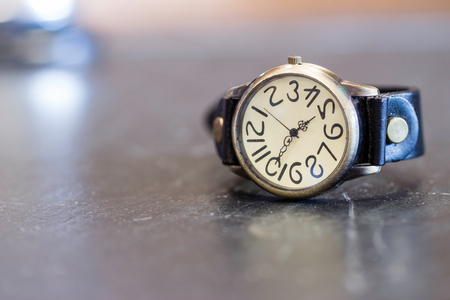 Old wrist watch on black stone table with blurry background