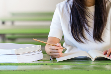 Asian woman writting on notebook on the table Stock Photo