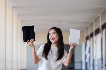 Asian woman holding tablet and book in school hallway
