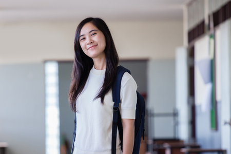 Happy asian woman with backpack stand in hallway