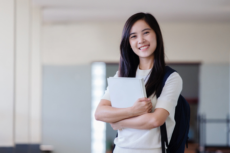 Asian woman stand in hallway holding book