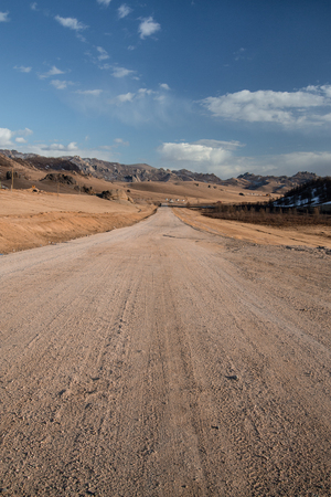 Sand road track outside country with mountain and blue sky Banque d'images