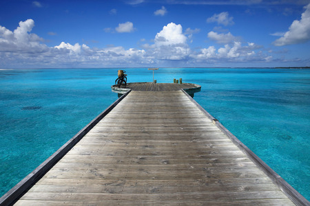 Wooden pier on the beach in the blue sea of Maldives photo