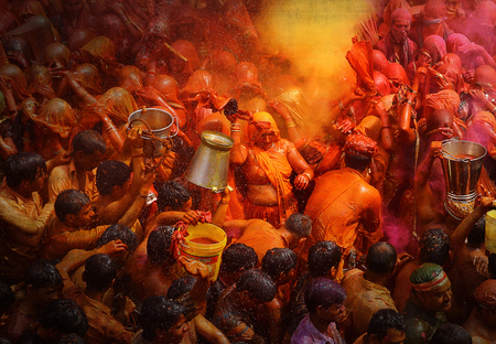 MATHURA,INDIA - 7/03/2015 : Indian devotees dance in colored water at the end of Holi celebrations, the Hindu festival of colors at the Baldev Temple.