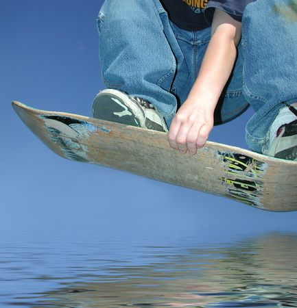 hydroplaning: youth jumping over water on skateboard deck