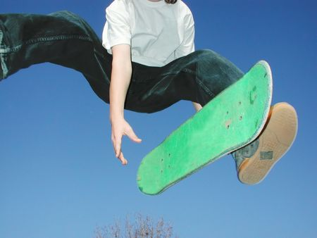 failed attempt: teen getting big air while missing a trick on a skateboard