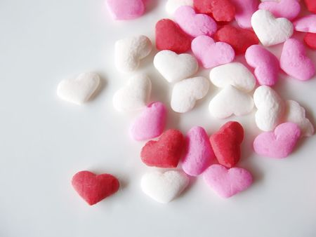 candied: pink, white and red candied heart spinkles on white background