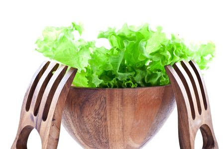 green lettuce leaves in a wood salad bowl with two big wood forks on a white background