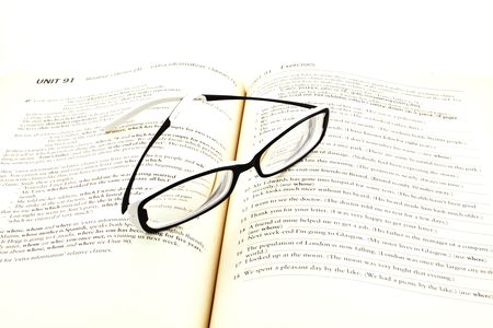 modern glasses on open english studying book photo