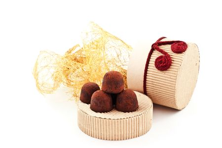 handmade truffles on a cover of gift carton. white background photo